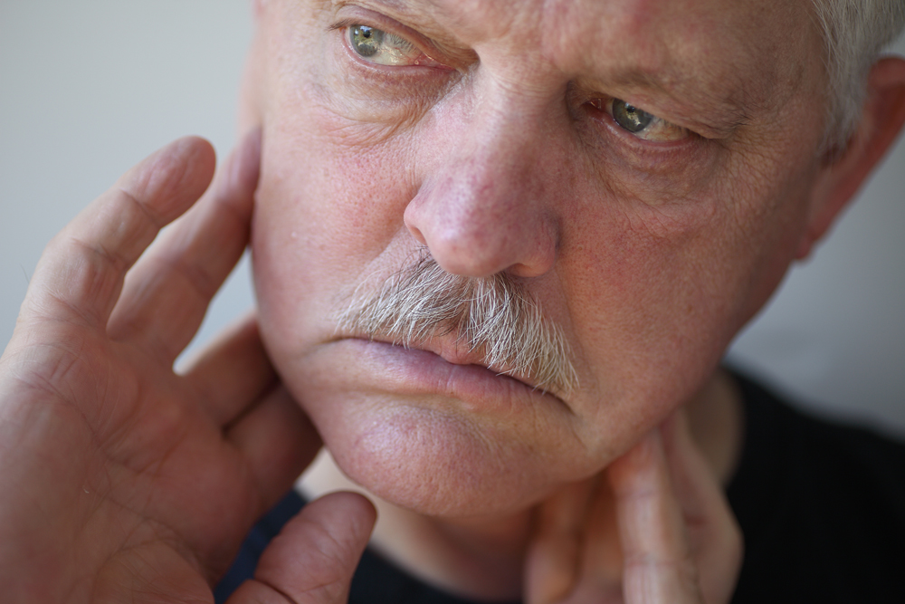 senior man touches his sore jaw area - Idaho Falls orthodontist