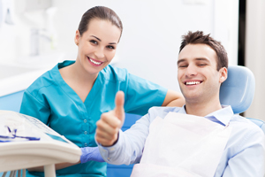 happy dental patient in dental chair with dental hygienist