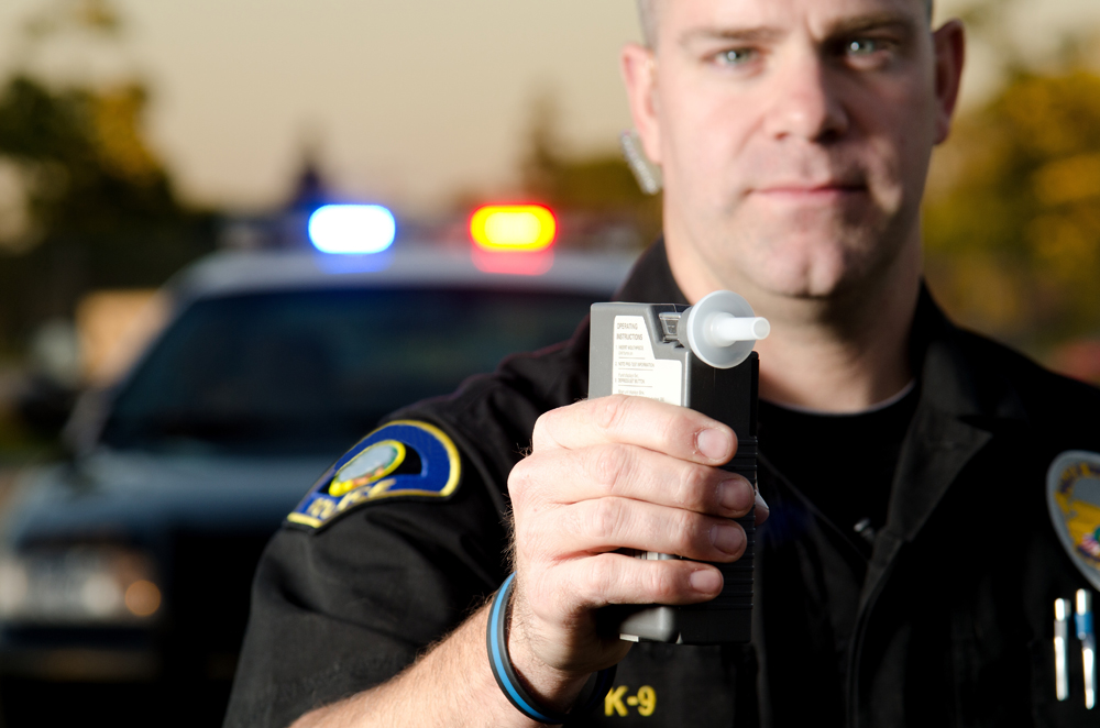 police officer holding breathalyzer - DUI attorney Springfield