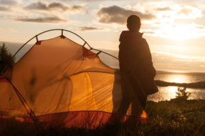 person camping with tent watching sunrise