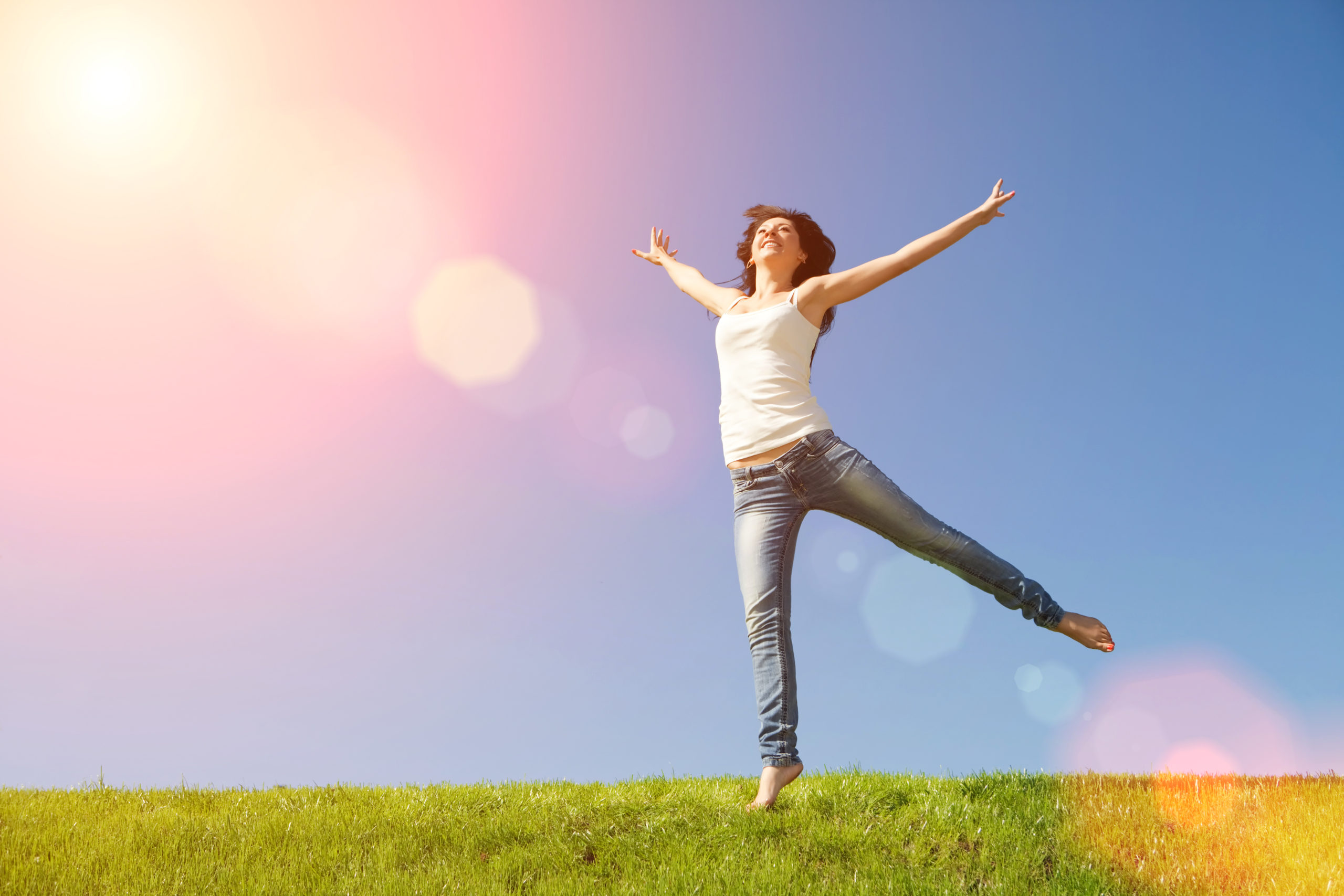 pretty young woman jumping on green grass - holistic thyroid