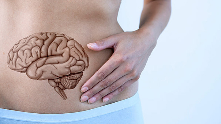 """woman with """"brain"""" on stomach - gut health concept"""