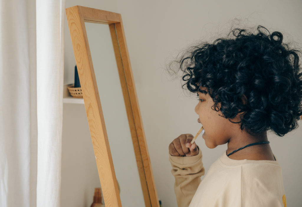 child brushing teeth in front of mirror