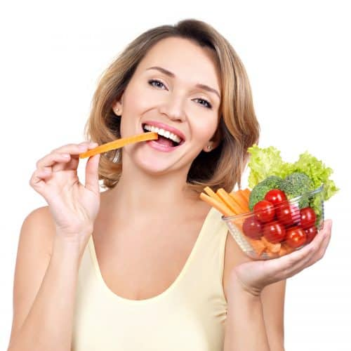 woman smiling eating a carrot